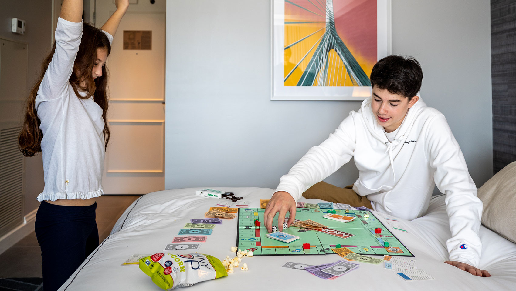 kids playing Monopoly on a guest room bed