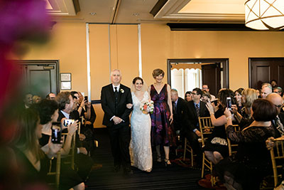 Bride walking down aisle with family