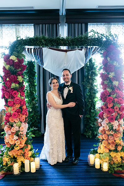 Wedding couple under floral arch