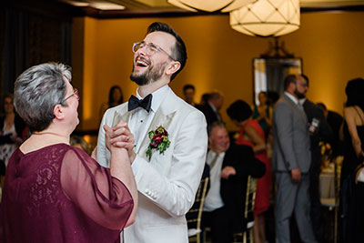Groom laughing while dancing