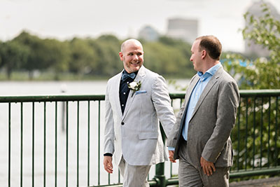 Grooms holding hands in wedding attire