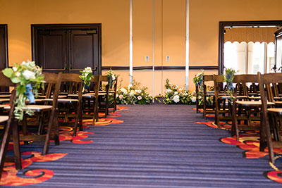 Wedding aisle with chairs and floral pieces