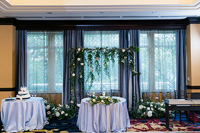 Wedding reception table with floral pieces in background