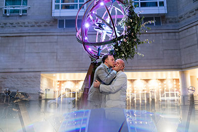 Grooms kissing in hotel courtyard