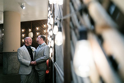 Grooms embracing each other in hotel courtyard